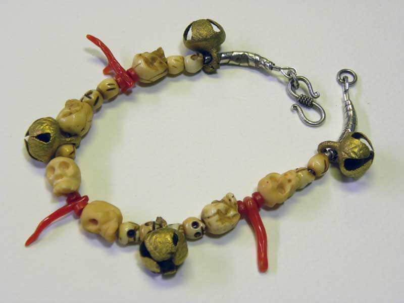 Brass Bells, Carved Bone Skulls, Red Coral, Sterling Silver clasp